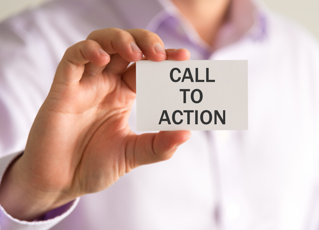 Closeup on businessman holding a card with CTA CALL TO ACTION message