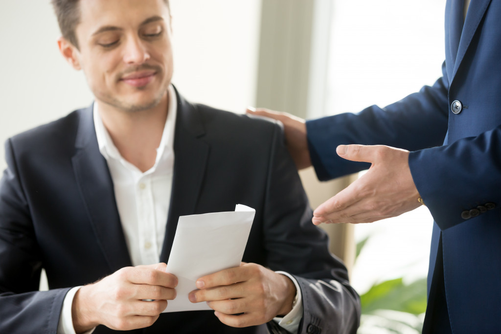 employee being handed a paycheck