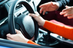 woman holding the car's steering wheel with help